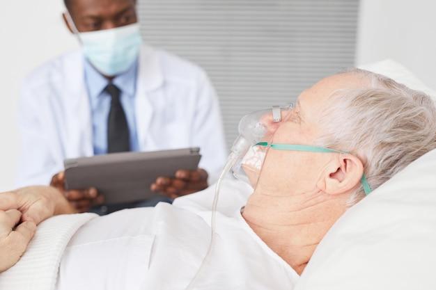 側面図は、バックグラウンドで酸素マスクとアフリカ系アメリカ人の医師、コピースペースと病院のベッドに横たわっている年配の男性のクローズアップ