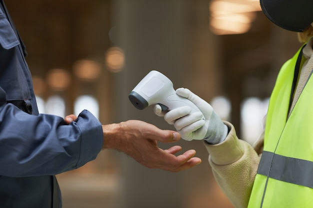 손을 가리키는 비접촉식 온도계로 작업자의 온도를 측정하는 감독자의 측면보기 닫습니다.