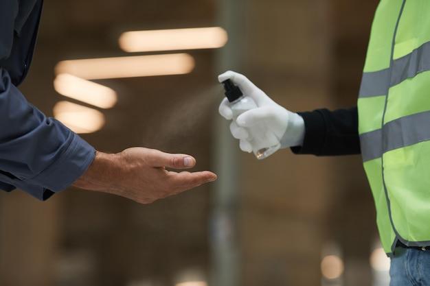 스프레이, 코로나 바이러스 안전으로 작업자의 손을 소독하는 감독자의 측면보기 닫기