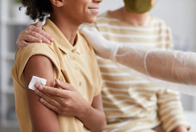 男性の看護師が彼を祝福しているクリニックでの共同ワクチン接種後に笑っている10代のアフリカ系アメリカ人の少年の側面図のクローズアップ