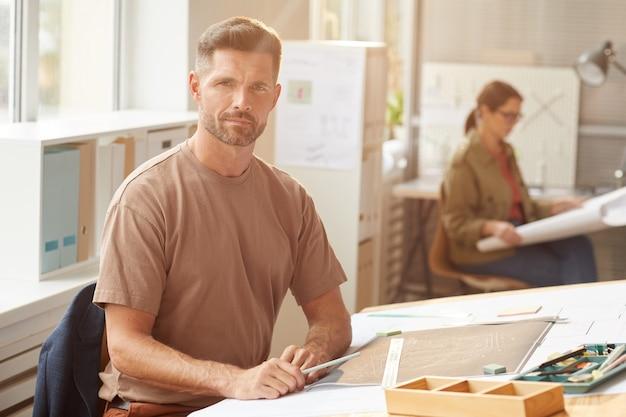 Вид сбоку крупным планом неузнаваемого мужского архитектора, рисующего чертежи и планы на рабочем месте,