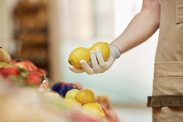 ファーマーズマーケットの果物と野菜のスタンドで新鮮な黄色のレモンを保持している認識できない男の側面図
