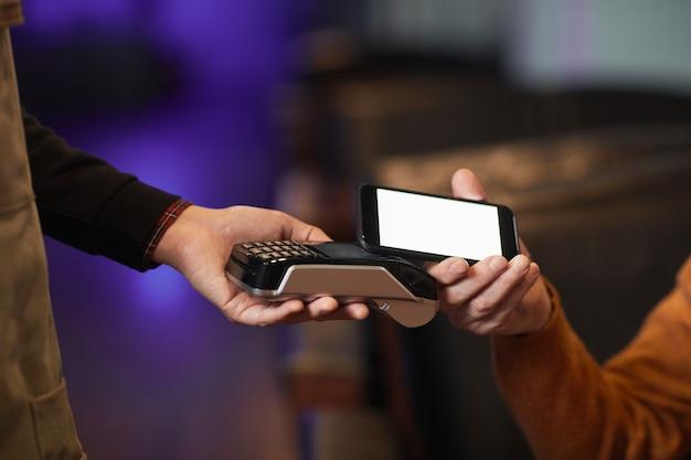 Вид сбоку крупным планом неузнаваемого зрелого мужчины, оплачивающего через nfc со смартфоном, сосредоточиться на руке, держащей телефон над терминалом, скопировать пространство