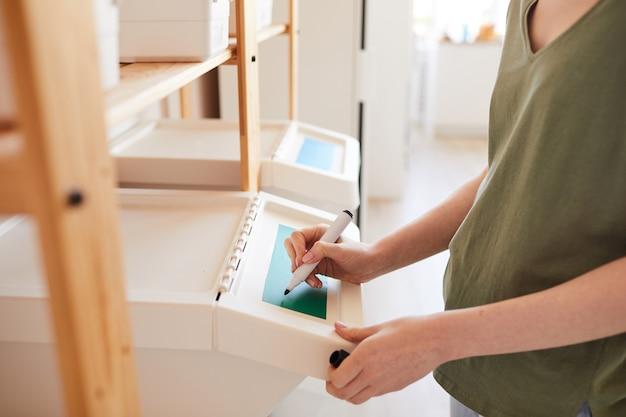집에서 저장 및 폐기물 분류를 관리하면서 집에서 플라스틱 쓰레기통에 라벨을 부착하는 인식 할 수없는 여성의 측면보기 닫기