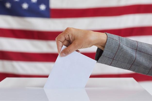 Вид сбоку крупным планом неузнаваемой женщины, помещающей бюллетень для голосования в урну для голосования, стоя против американского флага в день выборов, скопируйте пространство