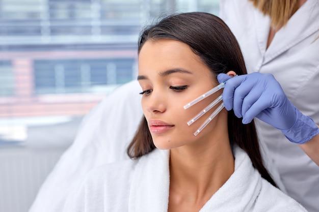 Крупным планом фото молодой брюнетки, вид сбоку, пришла к косметологу за ниткой pdo, процедурой нитевого лифтинга. эстетическая красота против старения, операция по подтяжке лица. выбираем лучшую нить