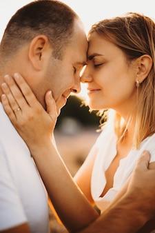 Вид сбоку крупным планом портрет прекрасной кавказской взрослой пары, сидящей лицом к лицу с закрытыми глазами, улыбаясь против заката.