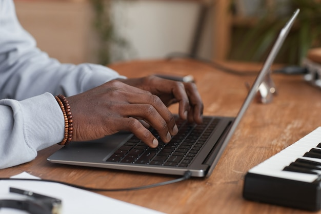 Side view close up of young african-american musician using laptop while composing music at home, copy space