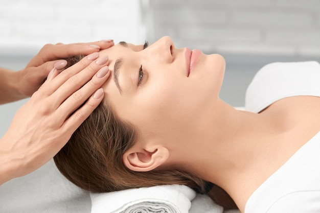 Side view close up of young beautiful woman lying on procedure massage for face