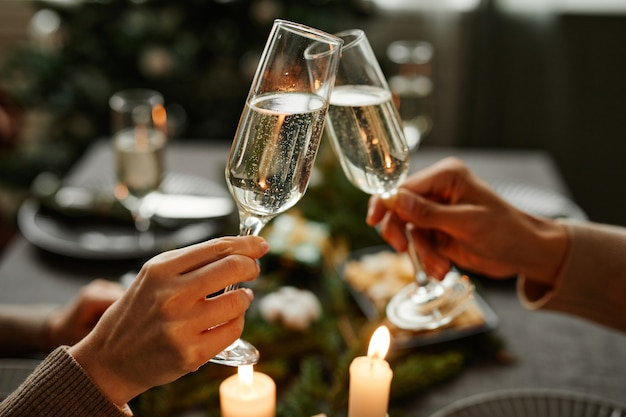 Side view close up of young couple clinking champagne glasses while enjoying christmas dinner togeth...