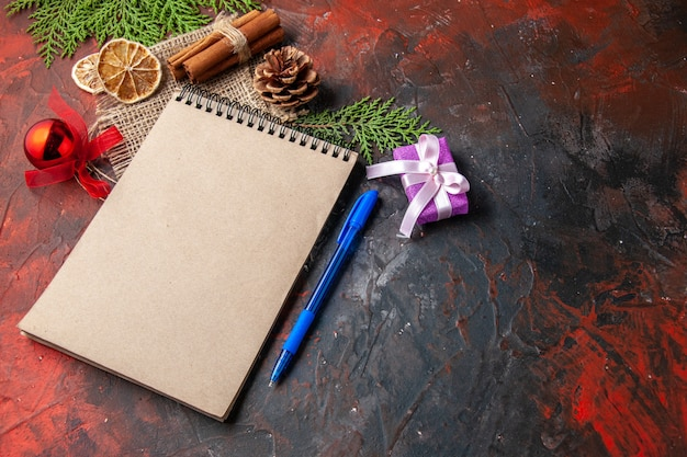 Side view of closed notebook with pen cinnamon limes gift conifer cone decoration accessory fir branche on dark background
