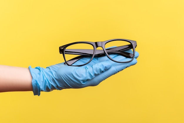 Крупный план взгляда сбоку человеческой руки в синих хирургических перчатках держа и давая черную рамку очков.