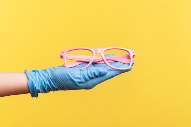 Крупным планом вид сбоку человеческой руки в синих хирургических перчатках, держа и давая розовую рамку для очков.