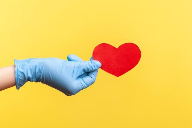 Крупным планом вид сбоку человеческой руки в синих хирургических перчатках, держа в руке маленькую красную форму сердца.