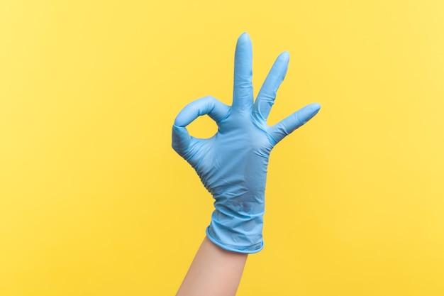 파란색 수술 장갑을 끼고 손가락으로 확인 표시 또는 3번을 보여주는 인간 손의 측면 보기.