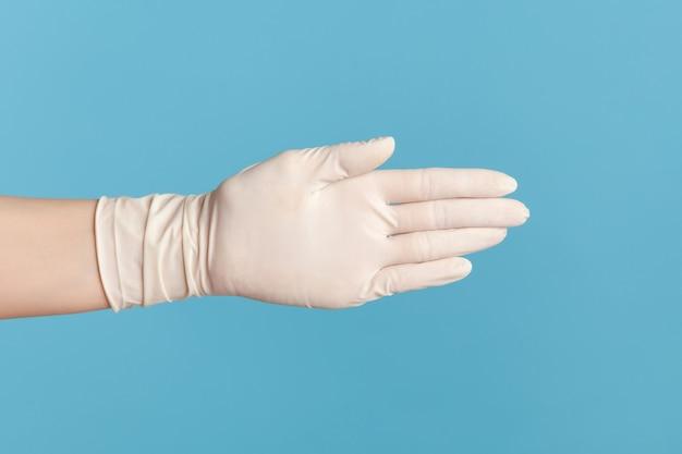 Крупным планом вид сбоку человеческой руки в белых хирургических перчатках, отдавая руку приветствию или касанию.