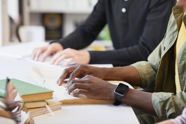 図書館で点字の本を読んでいる若い男と学生の包括的なグループの側面図のクローズアップ