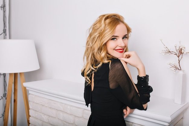 Side view closeup portrait of girl with blonde wavy hair in white modern room with floor lamp and fireplace. lady smiling, posing. wearing stylish black dress.