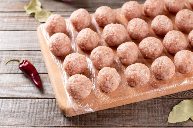 Side view closeup on raw semi-finished frozen meatballs on the wooden board with rice, onion and meat, horizontal