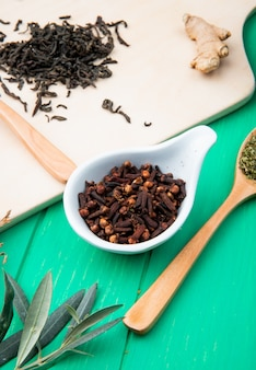 Side view of clove spice in a saucer and dry black tea leaves scattered on wood cutting board on gre