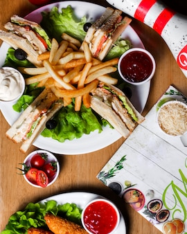 Side view of club sandwich with chicken french fries and sauces on wooden board