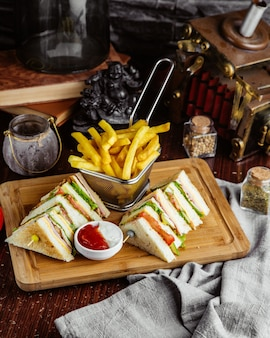 Side view club sandwich with french fries and ketchup with mayonnaise