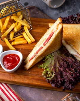 Side view of club sandwich with french fries and ketchup on wooden board