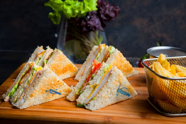 Side view club sandwich with french fries in wooden serving board