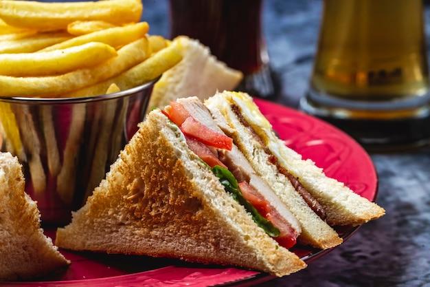 Боковой вид сэндвич с курицей-гриль, салатом из помидоров и картофелем фри на столе
