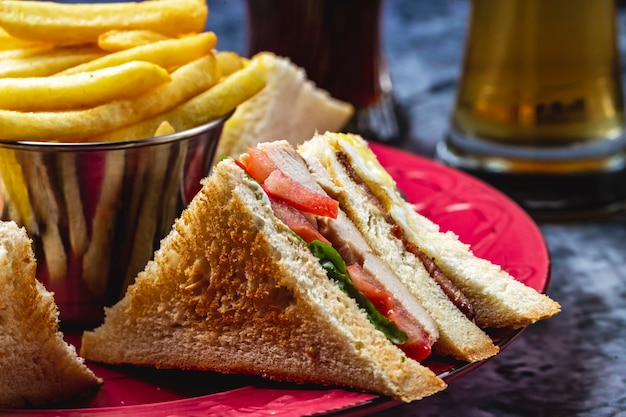 Side view club sandwich with grilled chicken tomato lettuce and french fries on the table
