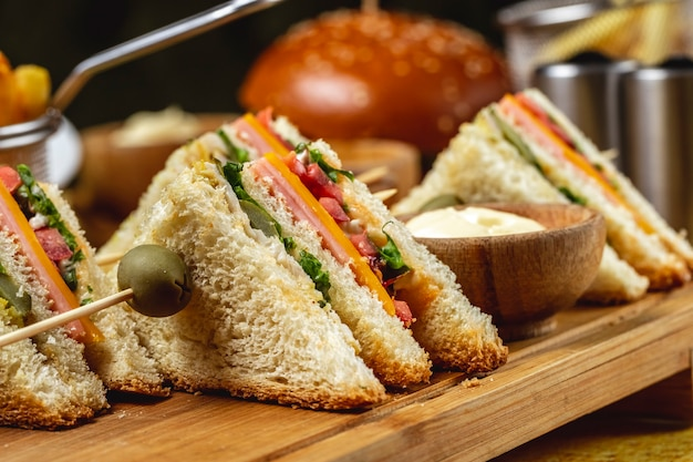 Side view club sandwich with ham pickled cucumber lettuce tomato cheese and sauce on a board