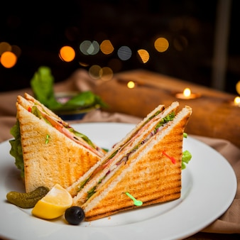 Side view club sandwich with salted cucumbers and lemon and olives in round white plate