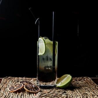 Вид сбоку коктейльная куба пинтада с трубочками для напитков и сушеным лимоном и лаймом в сервировочных салфетках