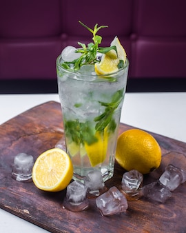 Side view of cocktail mojito with ice and lemon on a wooden board