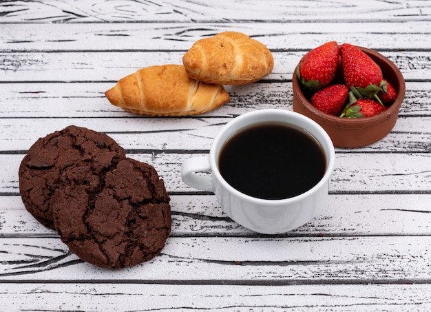 Side view of coffee with cookies and croissants with strawberry on white wooden surface horizontal