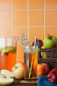 オレンジ色のタイルの背景にバスケットにリンゴとテーブルでサイドビュー冷たいリンゴジュース。テキストの垂直方向のスペース
