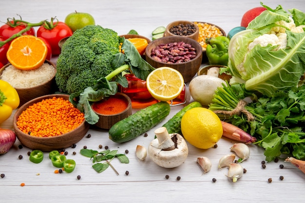 Vista laterale della raccolta di cibi freschi e spezie verdure su sfondo bianco