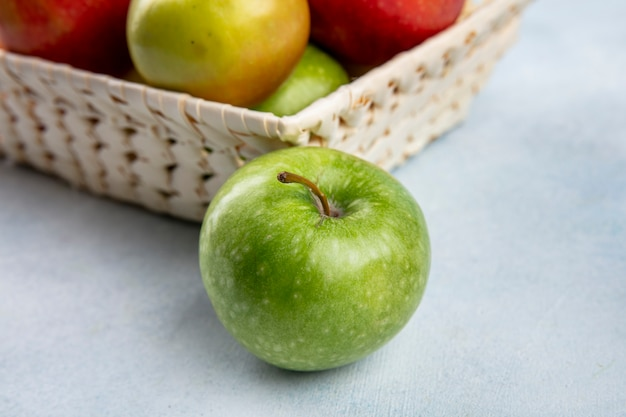 Вид сбоку цветные яблоки в корзине