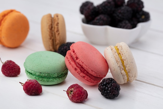 Side view of colored macarons with blackberries and raspberries on a white surface