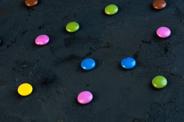 Side view of colorful candies scattered on black