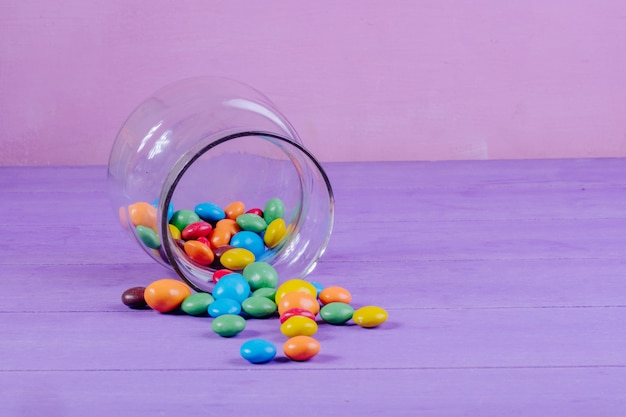 Side view of colorful candies scattered from a glass jar on purple background with copy space