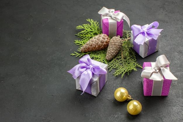 Vista laterale di regali colorati e accessori decorativi su sfondo scuro