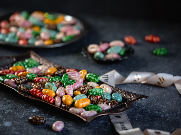 Side view of colorful glazed candies on a tray on black table