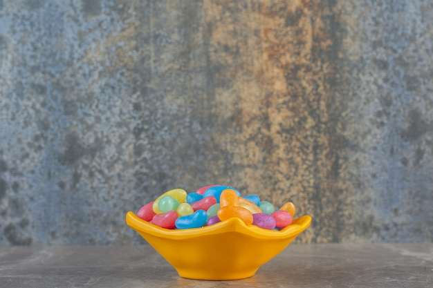 Side view of colorful jellybeans in orange bowl.