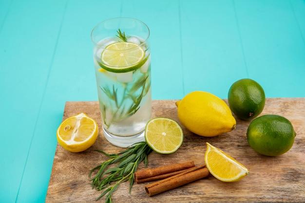 Vista laterale di limoni colorati con rinfrescante acqua estiva in un bicchiere su una tavola di cucina in legno con bastoncini di cannella sulla superficie blu