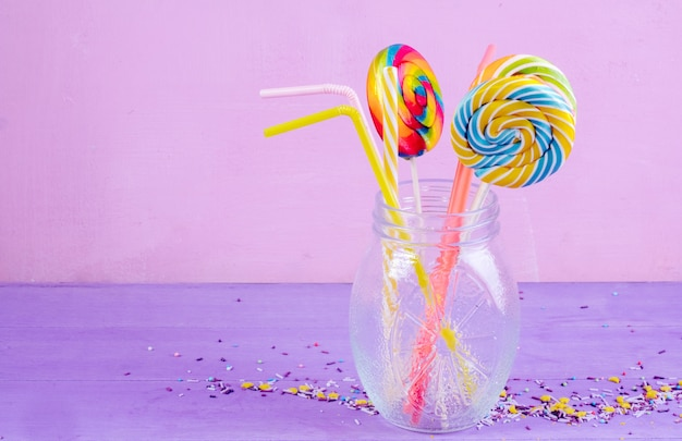 Side view of colorful lollipops in a glass jar and candy sprinkles on purple background with copy space