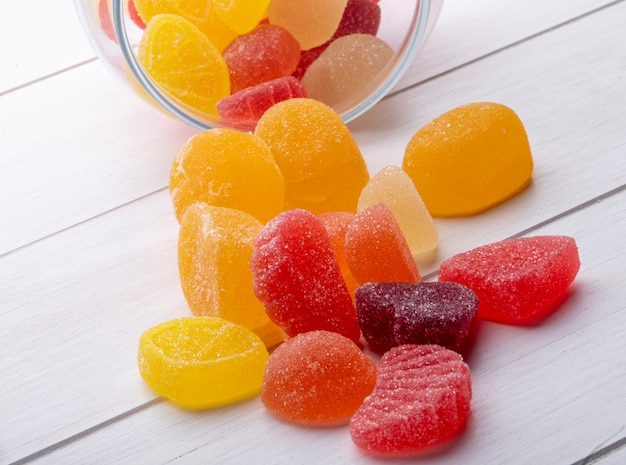 Side view of colorful marmalade candies scattered from a glass jar on rustic