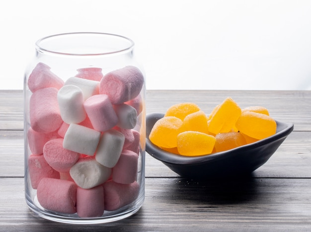 Side view of colorful marshmallow in a glass jar and marmalade candies in a bowl on wooden table