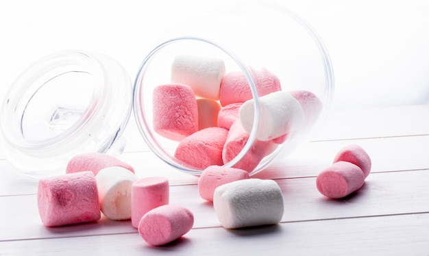 Side view of colorful marshmallow scattered from a glass jar on white