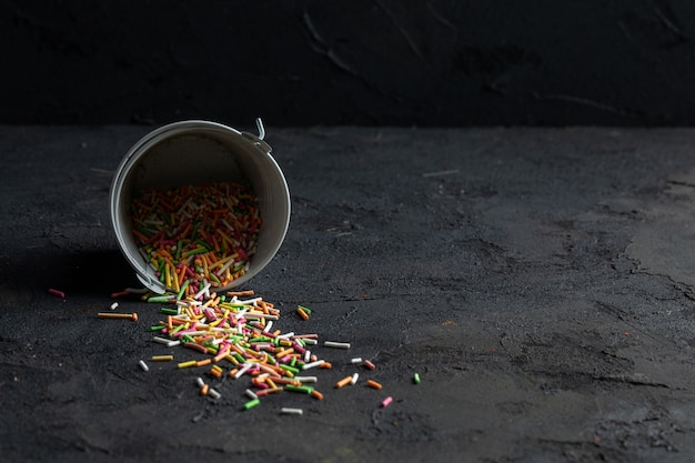 Side view of colorful sprinkles scattered from small bucket on black